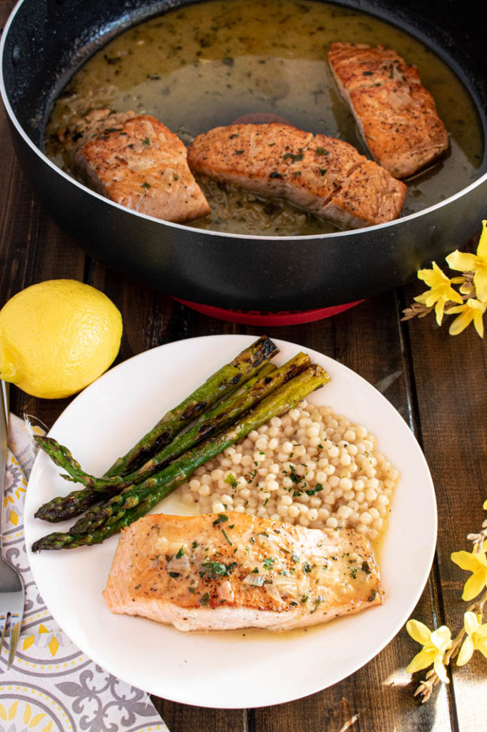 pan seared salmon with white wine lemon sauce on white plate with couscous and asparagus