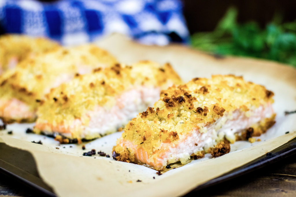 Horseradish crusted salmon on parchment paper with blue checkered towel and parsley in background
