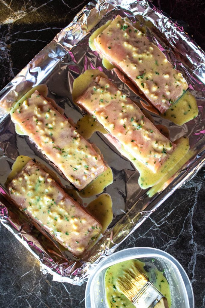 salmon on foil-lined baking sheet with honey dijon & garlic sauce spread on top, ready to go in oven