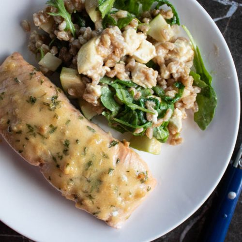 baked salmon with honey dijon and garlic on round white plate with farro salad on side