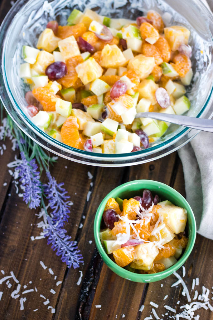 Vertical shot of large, clear glass bowl of Hawaiian Fruit Salad with khaki cloth, lavender stem, and shredded coconut surrouding it, and a small light green bowl of Hawaiian Fruit Salad in front