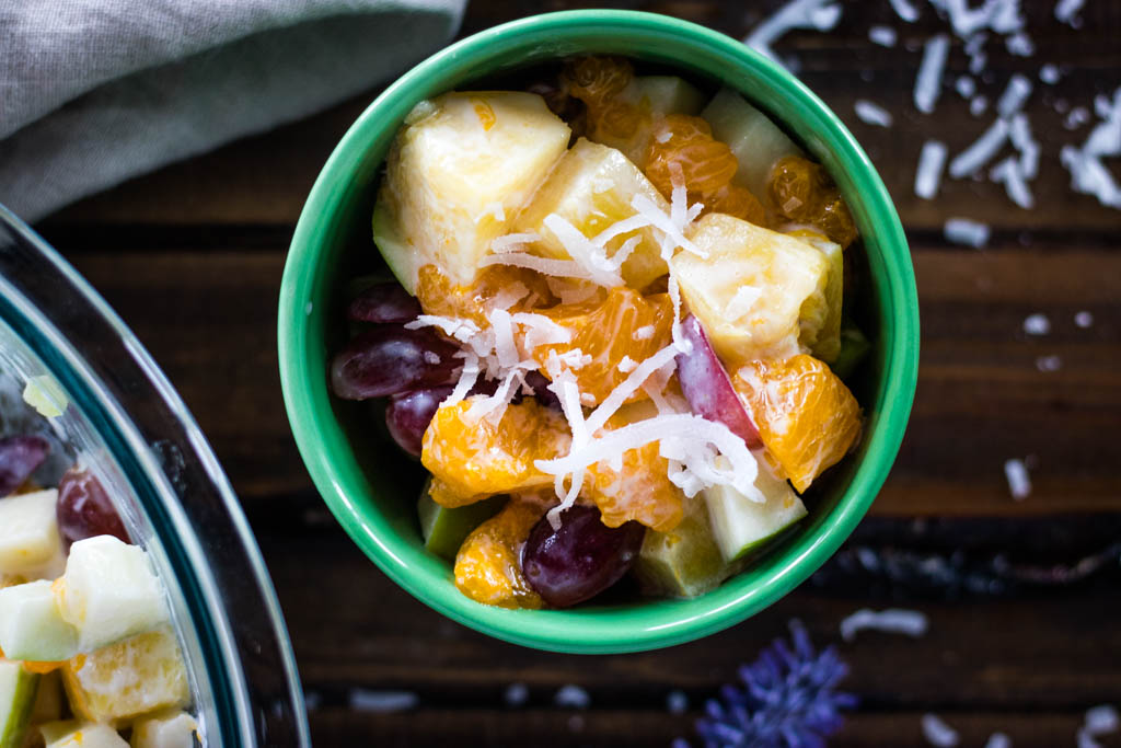 Top view, close up of small green bowl of Hawaiian Fruit salad, with shredded coconut, stem of lavender, and a khaki cloth surrounding it.