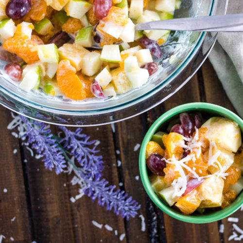 Top view big bowl of Hawaiian Fruit Salad with lavender and shredded coconut sprinkles and a smaller green bowl of fruit salad