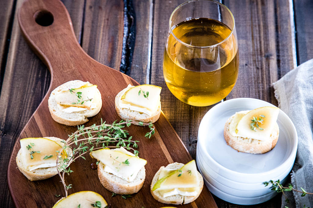 Assembled brie and pear crostini on serving board with glass of winem, sprigs of thyme, and a plated crostini