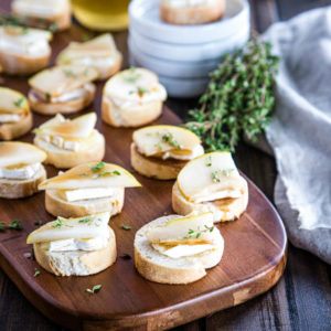 Serving board of brie and pear crostini with honey-balsamic glaze and fresh thyme