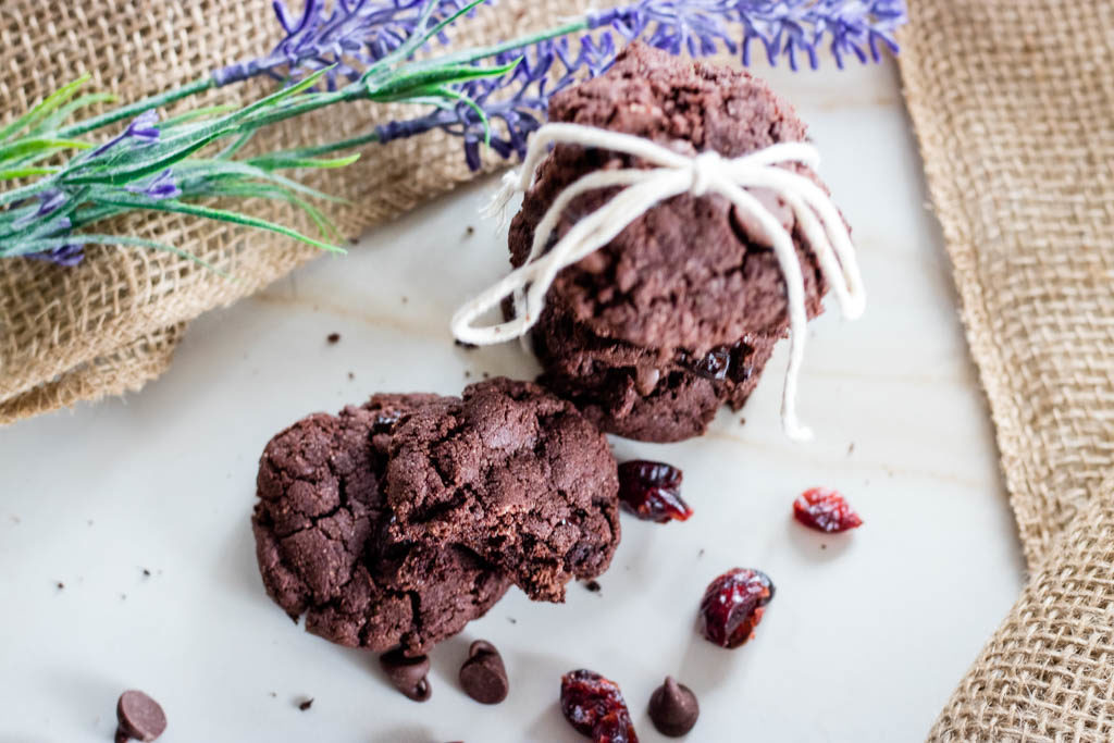 stack of chocolate cherry cookies tied with a bow, a broken cookie beside the stack to show the inside, and lavender flowers in the background