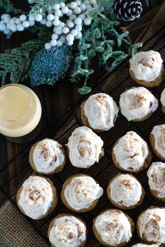 Eggnog Cookies with glass of eggnog and pine cone decorative greesn in back