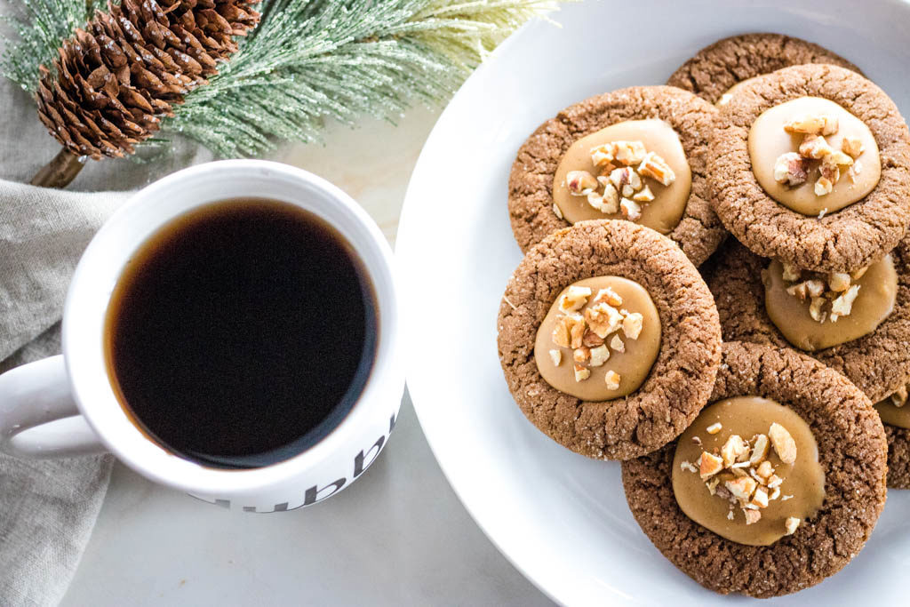 Plate of pecan gingerbread thumbring cookies next to a cup of coffee with pine cone decor in background