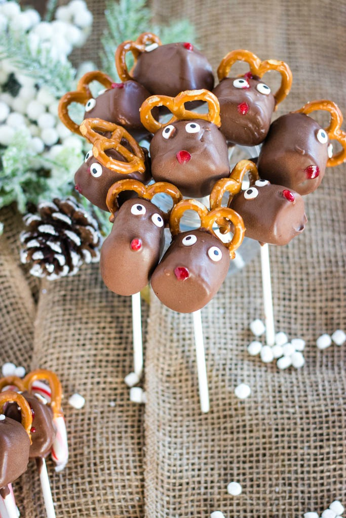 Huddle of chocolate reindeer marshmallow pops with mini marshmallow upright, with mini marshmallows and a few other marshmallow pops laying around them on burlap