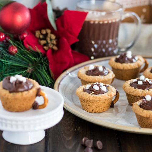 hot chocolate cookie cup on pedestal, next to plate of cookie cups, surrounded by chocolate chips, pretzels, poinsettia decor and cup of hot chocolate in background