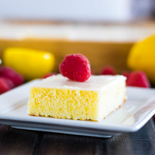Lemon brownie with glaze and raspberry on white plate with stack of plates, lemons, raspberries and pan of brownies in background