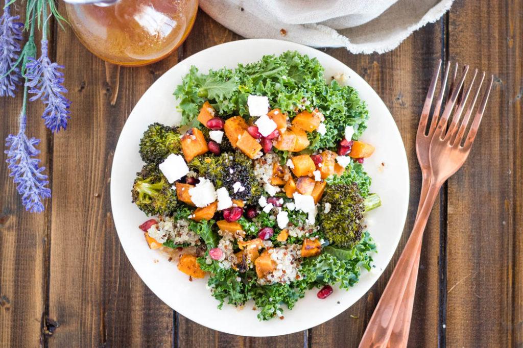 Roasted Winter Veggie & Quinoa Salad on white plate with copper forks, lavender stem and bottle of vinaigrette