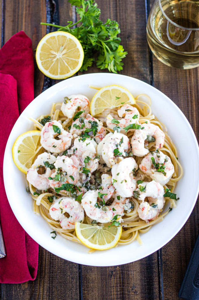 Shrimp Piccata over linguine in white bowl with lemon slices, parsley, red napkin and glass of wine