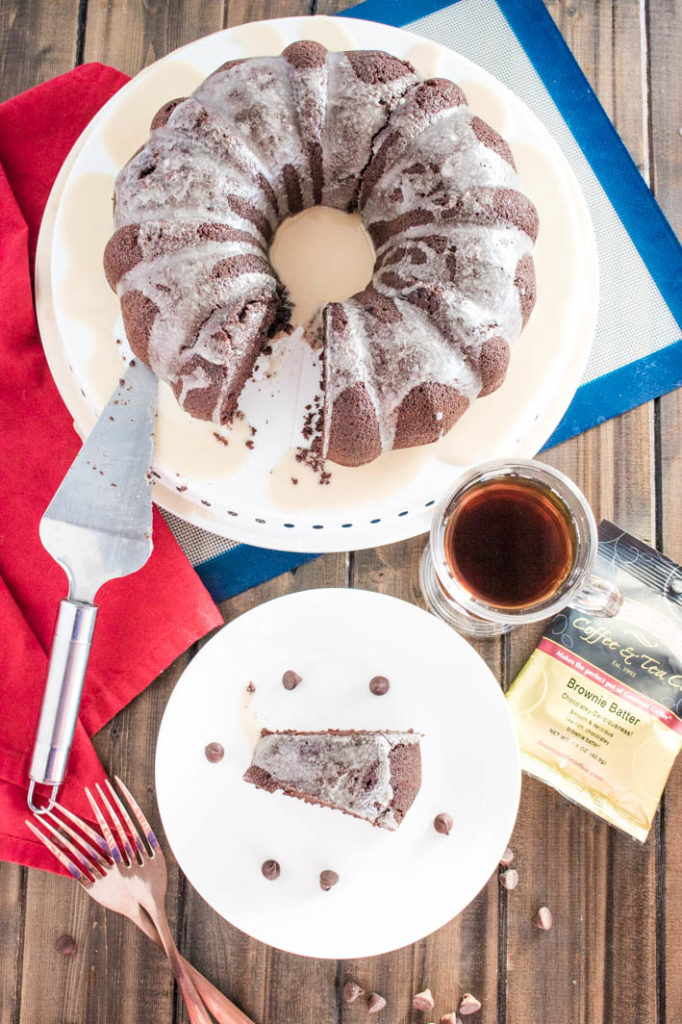 Slice of brownie batter mocha bundt cake with coffee glazeon white plate with chocolate chips, full cake behind, with cup of coffee