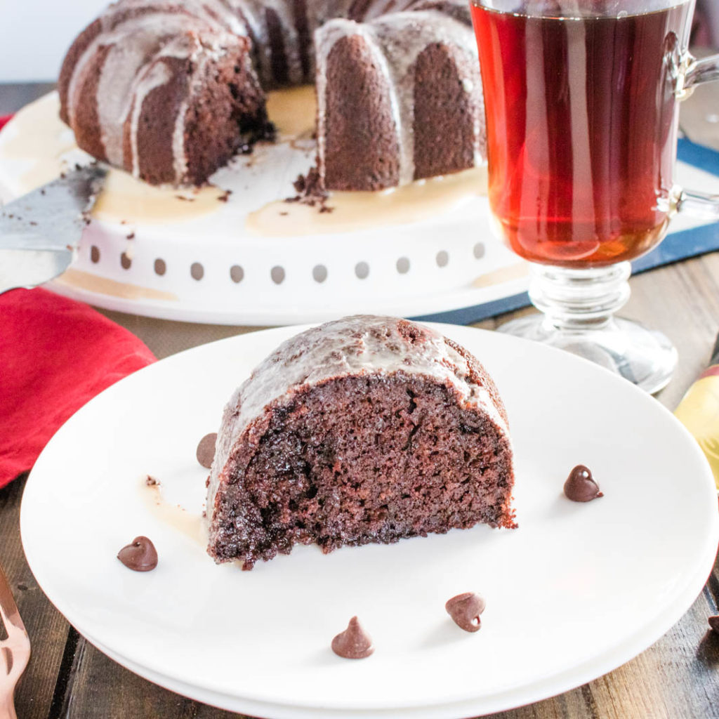 Slice of brownie batter mocha bundt cake on white plate with chocolate chips