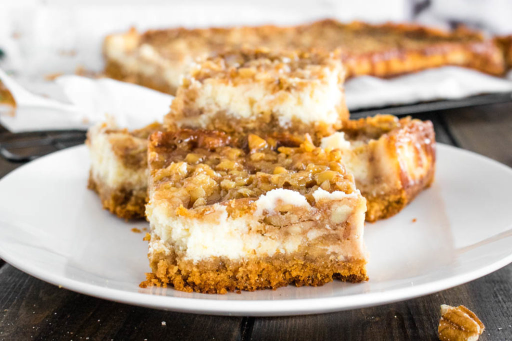 Cut pecan pie cheesecake bars on white plate
