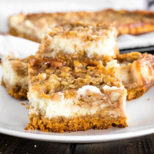 Cut pecan pie cheesecake bars on white plate