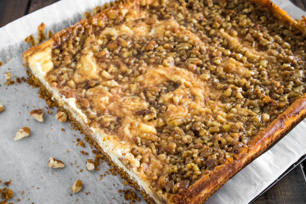 Uncut pan of pecan pie cheesecake bars
