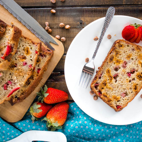 Slice of strawberry banana cinnamon chip bread on white plate with strawberry and fork