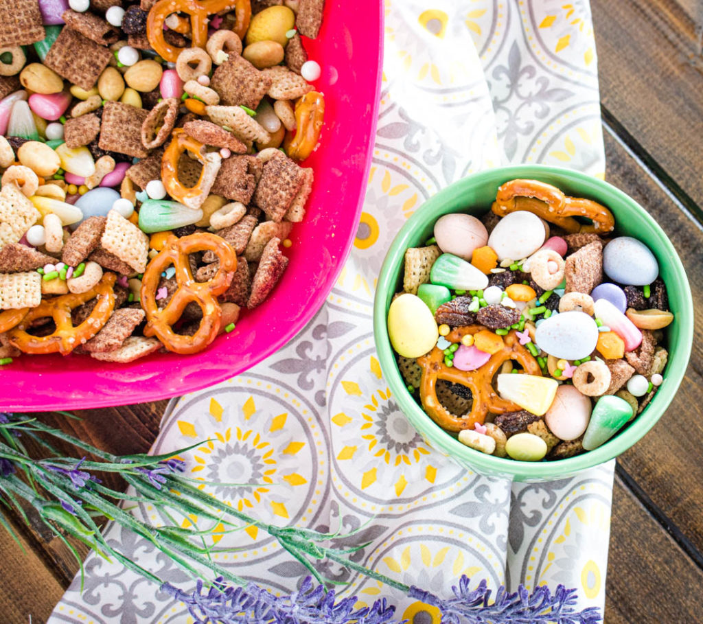 Easter snack mix in small green bowl, with yellow and gray towel, lavender stem, and large pink bowl of snack mix