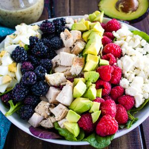 chicken cobb salad with berries in white bowl with avocado and glass bottle of dressing in background
