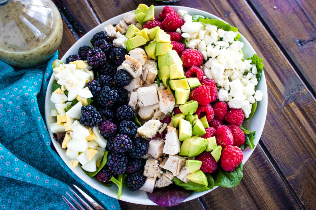 chicken cobb salad with berries in white bowl with bottle of dressing in background