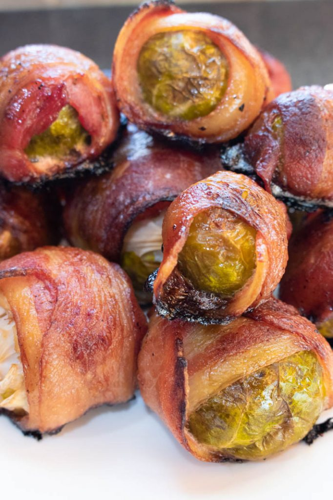 bacon wrapped brussels sprouts stacked on round white plate