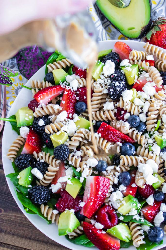 Balsamic Lemon Poppyseed Vinaigrette pouring onto summer berry spinach pasta salad