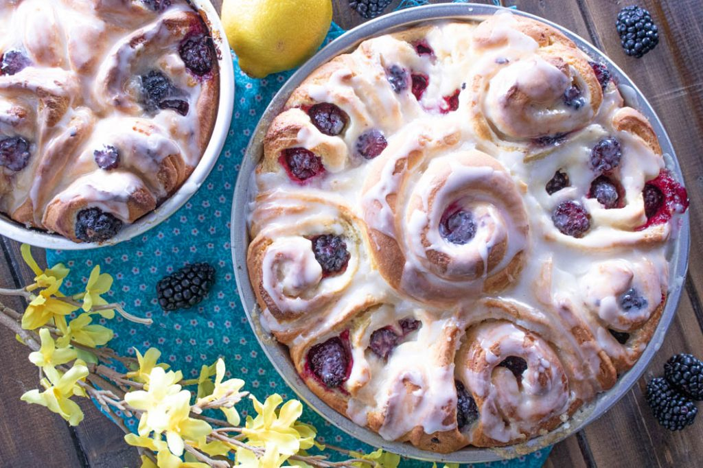 Blackberry Lemon Sweet Rolls in pan with yellow flowers and lemon