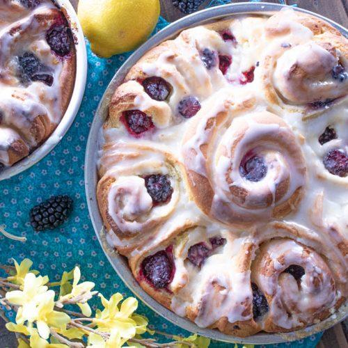 Blackberry Lemon Sweet Rolls in pan with yellow flowers and lemon