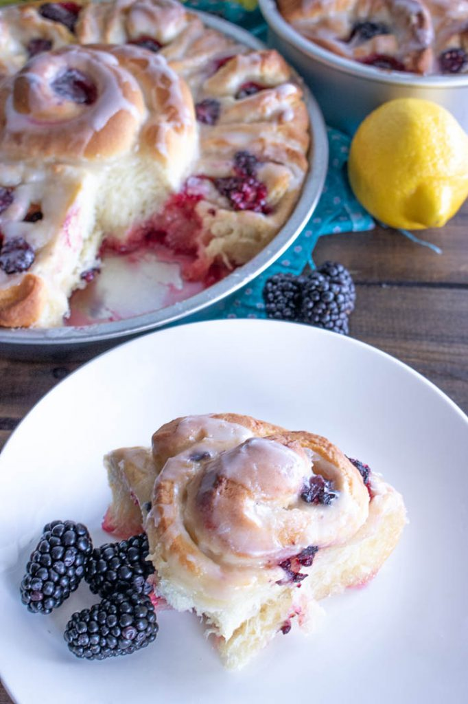 Blackberry Lemon Sweet Roll on white plate with pan of sweet rolls and lemon behind