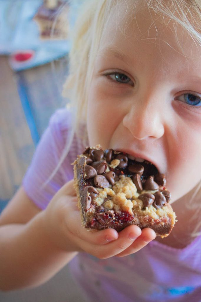 little girl taking a bite of a chocolate raspberry crumb bar