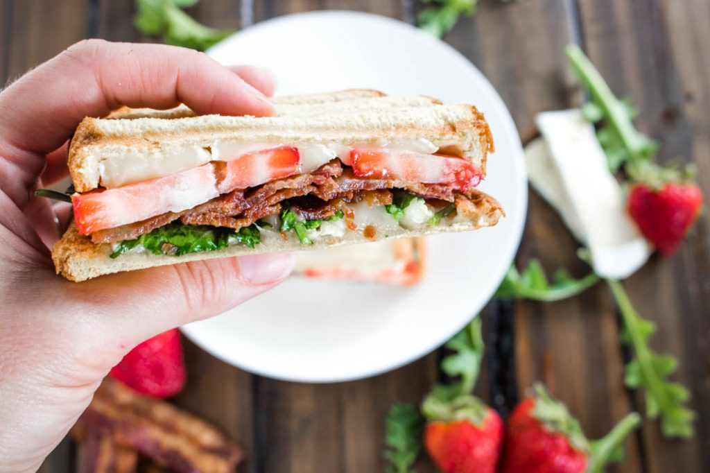 Half of a Strawberry Bacon Brie Panini, held in a hand with a white plate, strawberries, arugula leaves, slices of brie and bacon scattered below