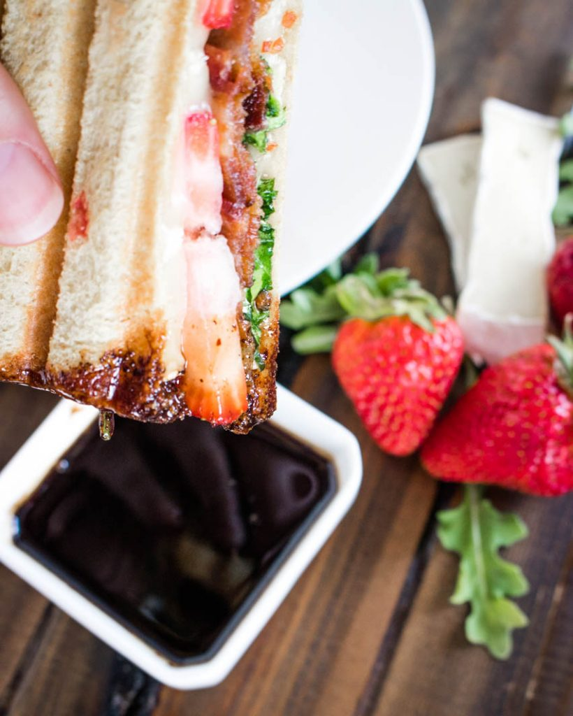 Half of a Strawberry Bacon Brie Panini with balsamic honey sauce on the corner, held in a hand with a bowl of balsamic honey sauce below and a white plate, strawberries, arugula leaves, slices of brie and bacon below