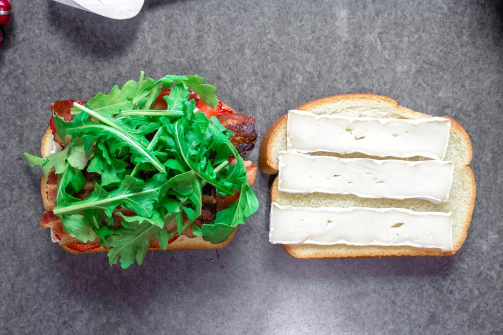 Open sandwich with brie on one slice of bread and arugula on top of bacon, strawberries and more brie on the other slice