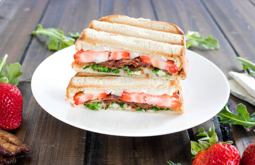 Strawberry Bacon Brie Panini, cut in half on white plate with strawberries, arugula leaves, slices of brie and bacon scattered around the plate