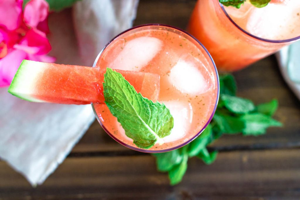 Glass of minty watermelon agua fresca with watermelon slice and mint garnish, on brown wood table.