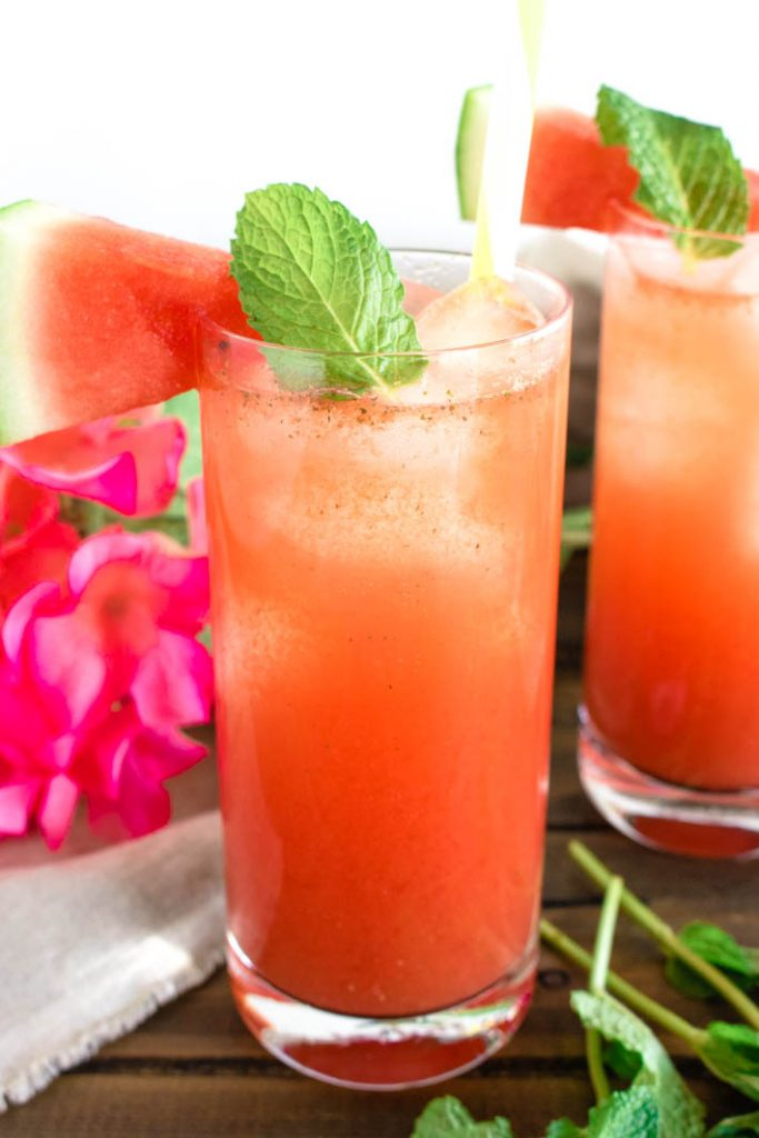 Two glasses of minty watermelon agua fresca with watermelon slice and mint garnish, on brown wood table.