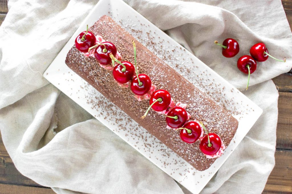 Chocolate cherry cake roll on white plate with powdered sugar and chocolate shavings, topped with fresh cherries