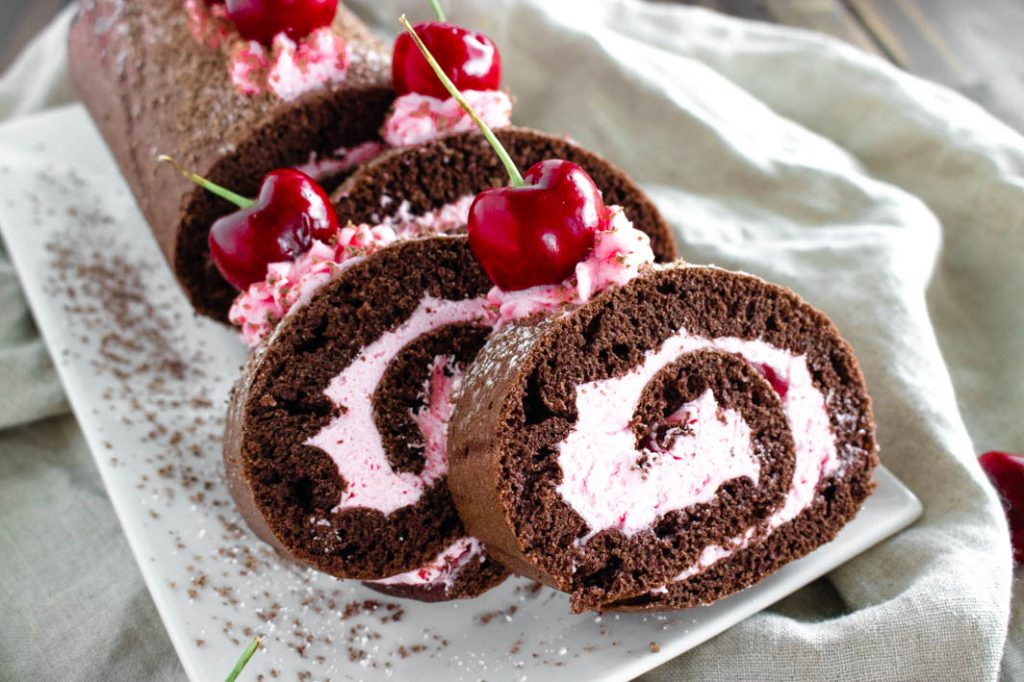 Chocolate cherry cake roll, three slices, on white plate with  powdered sugar and chocolate shavings, topped with fresh cherries