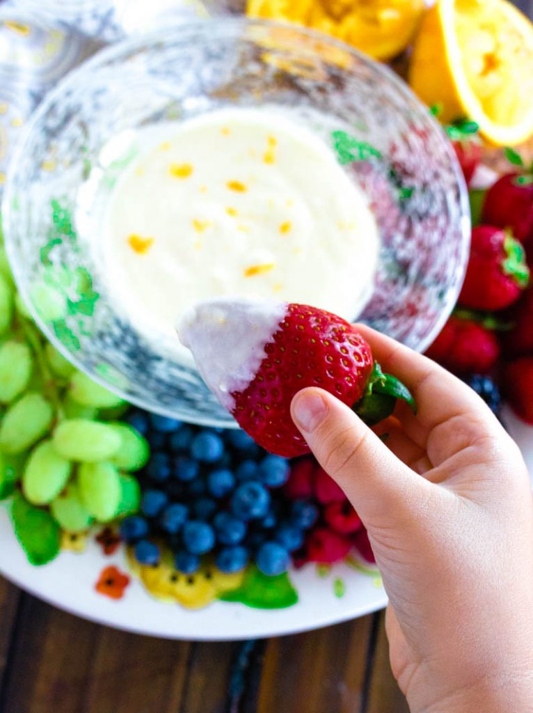 Little hand holding a strawberry dipped in orange creamsicle fruit dip with fruit dip in glass bowl with variety of fruits on a platter beneath