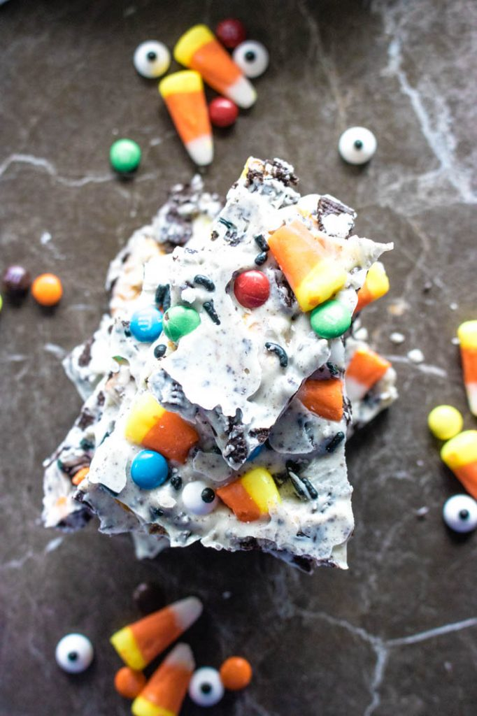 stack of spooky candy bark with loose candies scattered around on table