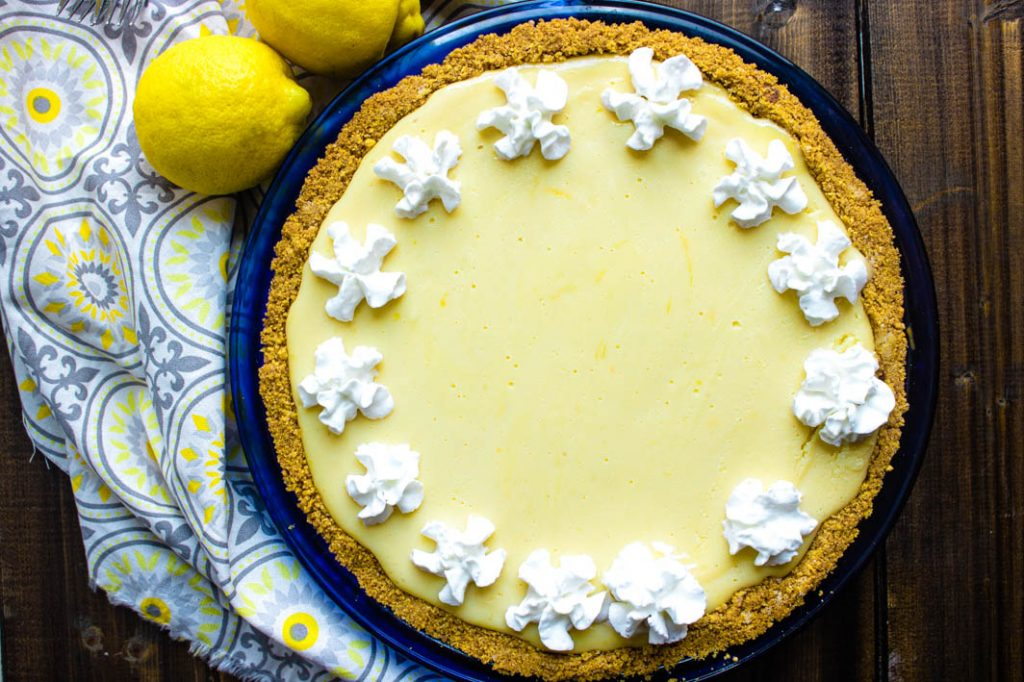 Lemon icebox pie with whipped cream stars on top. White, grey and yellow cloth and whole lemons on left side.